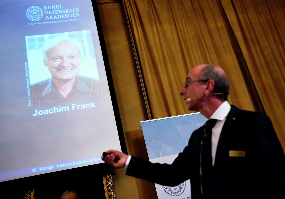 Peter Brezezinski (R), member of the Nobel Committee for Chemistry, presents the work of Joachim Frank from the US, one of the three winners of the 2017 Nobel Prize in Chemistry on October 4, 2017 at the Royal Swedish Academy of Sciences in Stockholm, Sweden. Scientists Jacques Dubochet from Switzerland, Joachim Frank from the US and Richard Henderson from Britain won the Nobel Chemistry Prize for the development of cryo-electron microscopy, a method of simplifying and improving the imaging of biomolecules. / AFP PHOTO / Jonathan NACKSTRANDJONATHAN NACKSTRAND/AFP/Getty Images