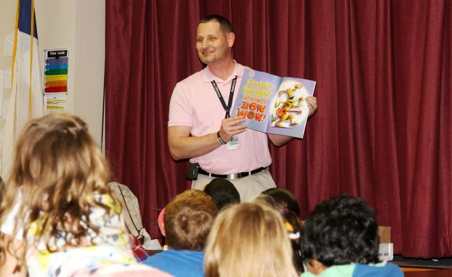 Mike Hicks, volunteer from Walmart Distribution Center, reads a book on Tuesday to La Mesa Elementary first grade students during the Read First program sponsored by the Hale County Literacy Council.
