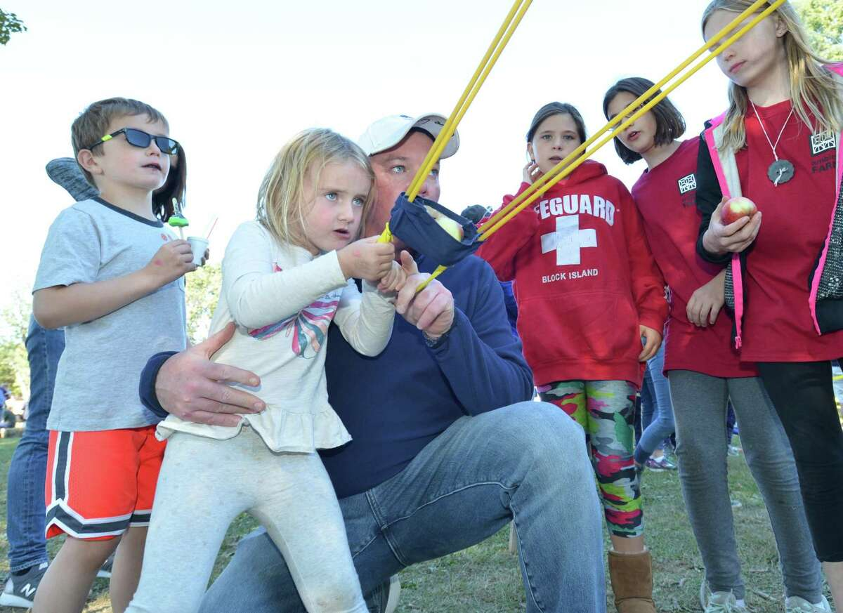 New Canaan's Avery Gallagher aims her apple slingshot with help from dad Brian and brother Brian and mom Suzanne during the 17th annual Ambler Farm Day at Ambler Farm on Sunday October 1, 2017 in Wilton Conn. Games, food and rides like apple slingshot, farm animals, scarecrows, hay rides, trebuchet punkin chucker, children's crafts, pumpkin patch, live music, homemade apple pies and baked goods, and more, along with pumpkin painting were just some of the many activities for everyone