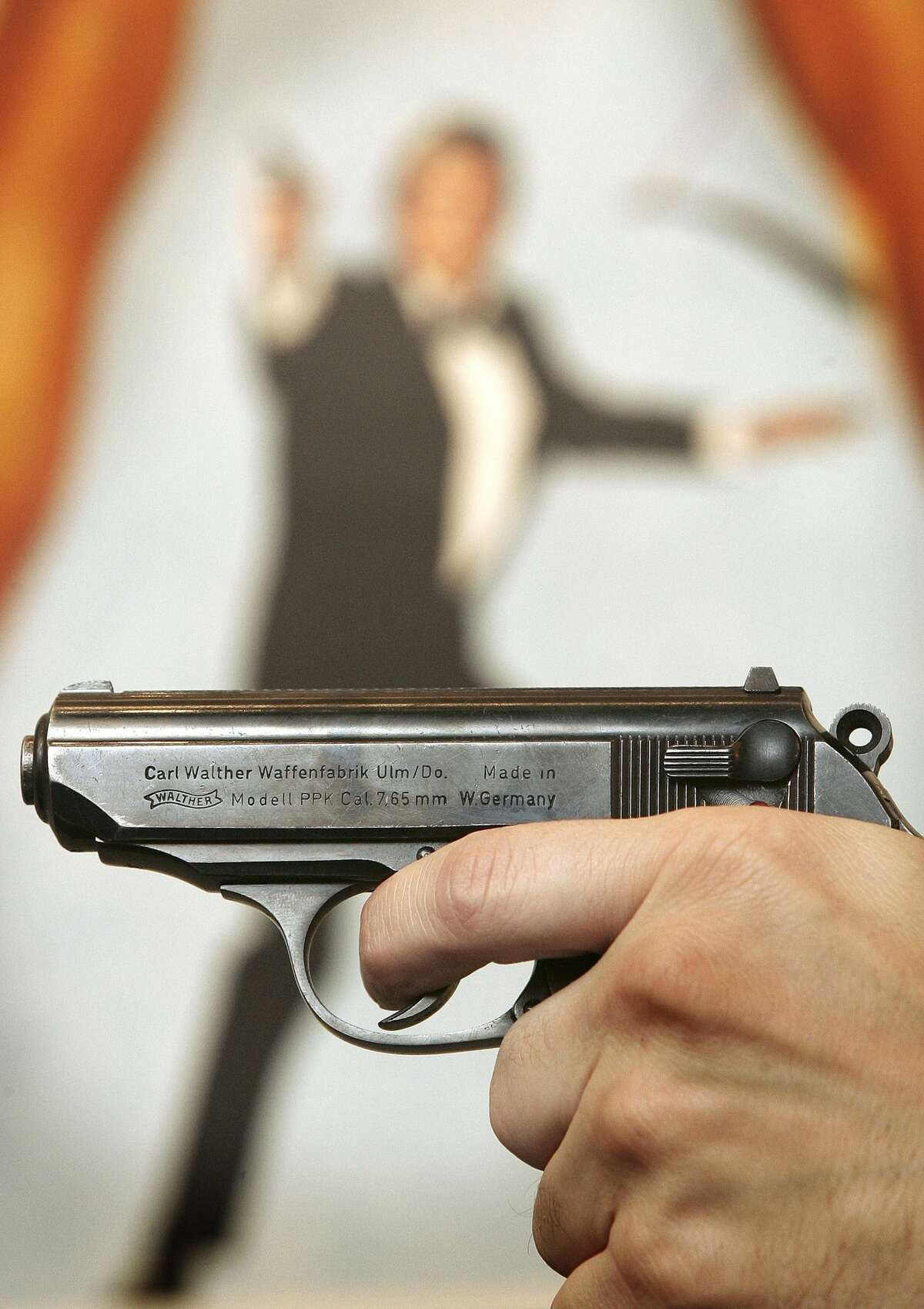 LONDON - NOVEMBER 02: A Walther PPK handgun is held up infront of a poster of the film 'For Your Eyes Only' during promotion of a sale of weapons from James Bond films on November 2, 2006 in London. Actor Daniel Craig will play Bond in 'Casino Royale' the 21st film made from author Ian Fleming's books. Christie's Film and Entertainment sale takes place on December 5, 2006. (Photo by Peter Macdiarmid/Getty Images)