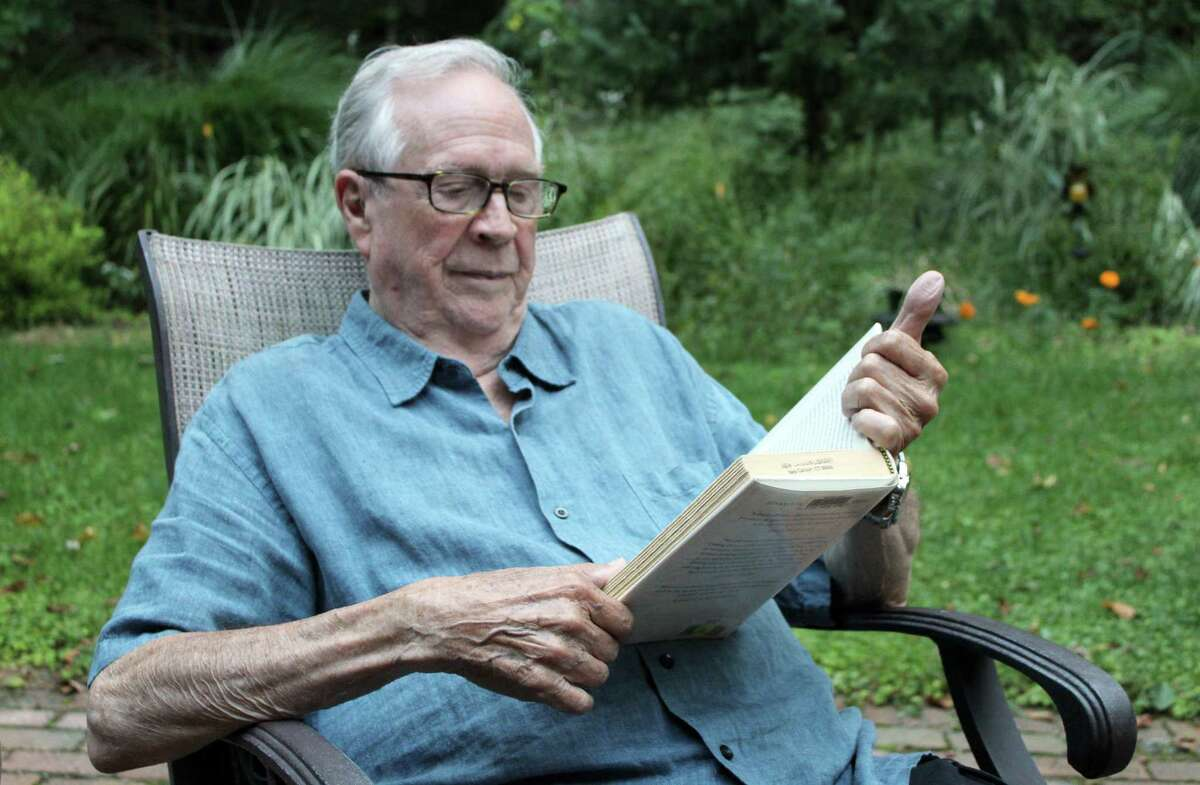 Gordon Nugent, 91, reads a book in his backyard at his Wilton home.