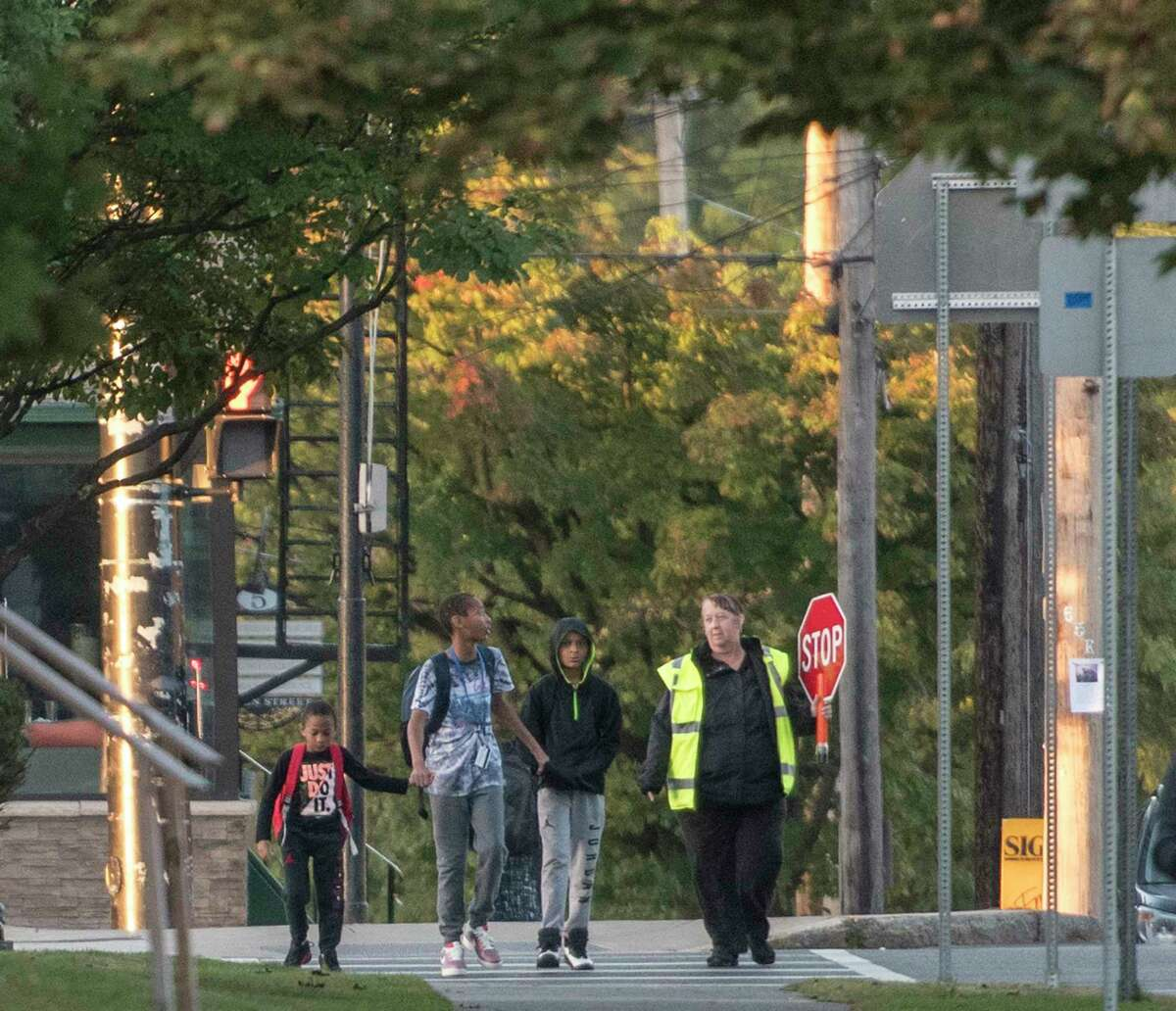 A crossing guard walks with students on their way to Pine Hills Elementary School on National Walk to School Day Wednesday Oct. 4, 2017 in Albany, N.Y. (Skip Dickstein/Times Union)