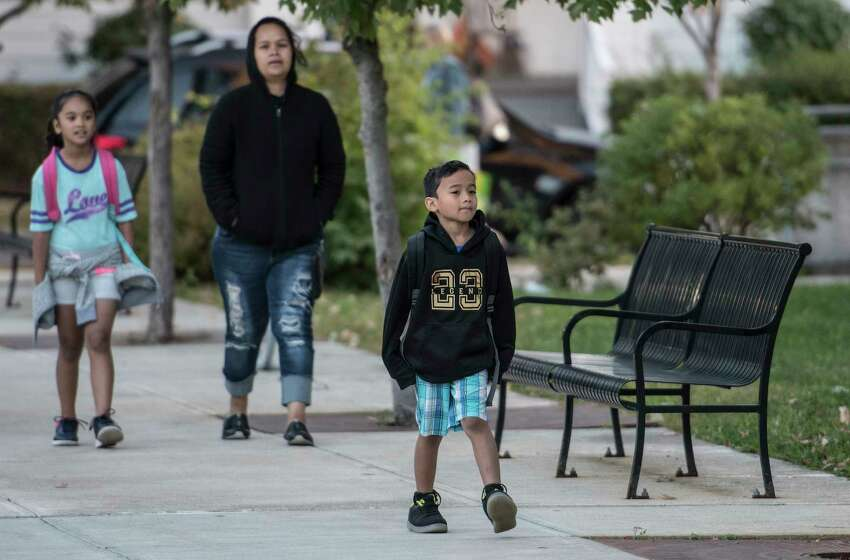 Margie Maipi walks with Lewin Ifenuk, 7, foreground and U-Me Ifenuk, 8, on their way to Pine Hills Elementary School on National Walk to School Day Wednesday Oct. 4, 2017 in Albany, N.Y. (Skip Dickstein/Times Union)