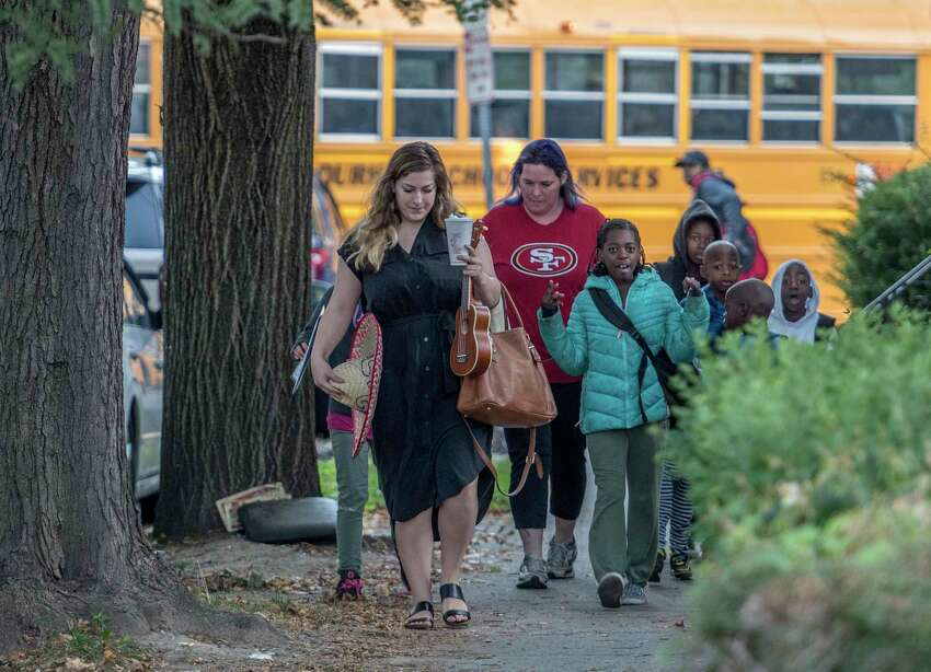 Students on their way to Pine Hills Elementary School on National Walk to School Day as a school bus passes behind them on Wednesday Oct. 4, 2017 in Albany, N.Y. (Skip Dickstein/Times Union)