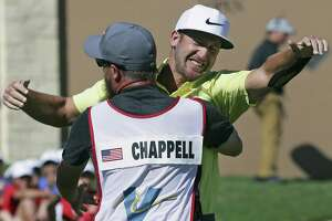 Kevin Chappell gets a hug from his caddy, Joe Greiner, after sinking a birdie putt on the 18th hole to win the Valero Texas Open on April 23, 2017, in San Antonio.