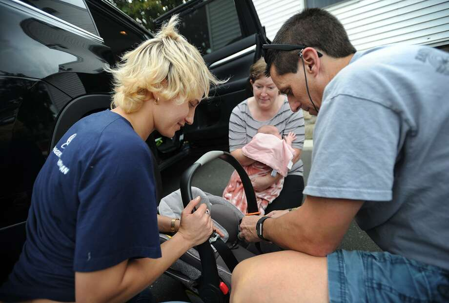 Child Passenger Safety Technician Adelle Zocher, left, and Easton Police Officer Mark Pastor, above, work on a car seat for Gabrielle Cweklinski, of Milford, during Griffin Hospital's Safe Kids Greater Naugatuck Valley Coalition's free Child Passenger Seat Check Clinic in Derby on Wednesday. At left, Safe Kids Greater Naugatuck Valley Coalition Coordinator Cathi Kellett donates a new car seat to a participant. Photo: Brian A. Pounds / Hearst Connecticut Media / Connecticut Post