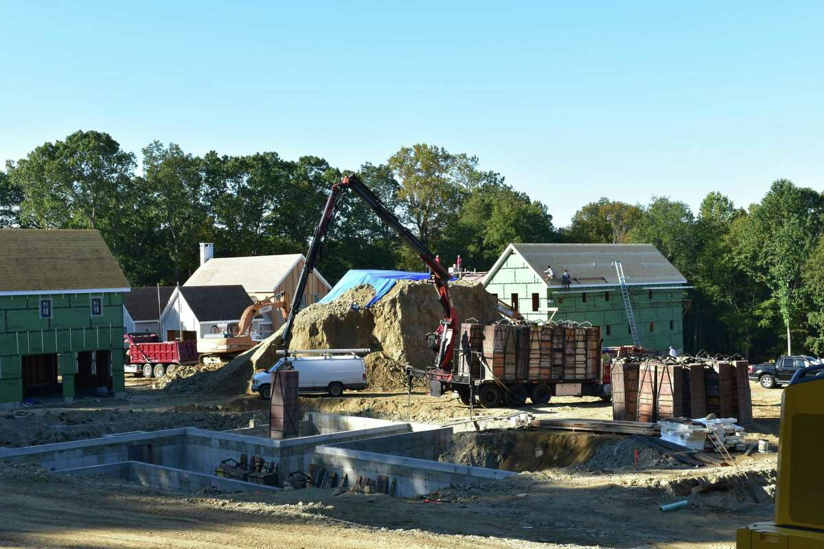 Construction crews work in early October 2017 on multiple new houses planned for a new subdivision on Chestnut Hill Road in Norwalk, Conn.