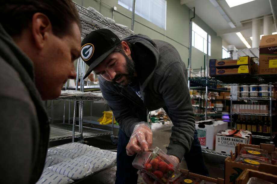 Michael Murphy (right), produce quality control and buyer, and Jason Crayne, receiving, inventory and quality control, look over a box of strawberries during a delivery at the Farmstead San Mateo hub. Photo: Lea Suzuki, The Chronicle