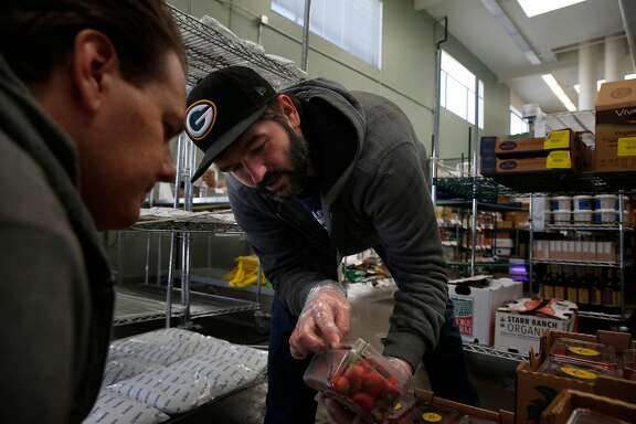 Michael Murphy (right), produce quality control and buyer, shows  Jason Crayne (left), receiving, inventory and quality control, a box of strawberries as they decide on which produce they'll accept  during a delivery at the Farmstead San Mateo hub on  Tuesday, October 3, 2017 in San Mateo, Calif.
