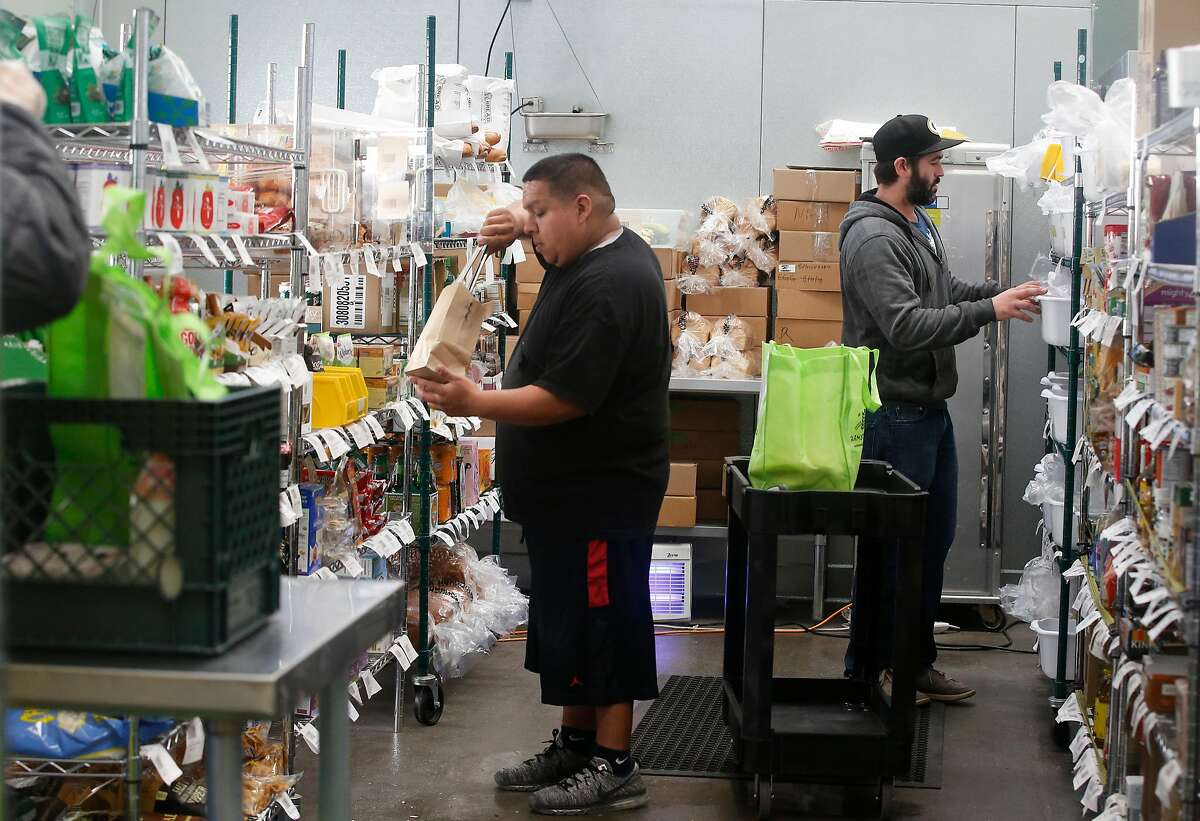Jose Flores (left), Farmstead associate, conducts an ambient pick and pack while Michael Murphy (right), produce quality control and buyer, checks items on a shelf at the Farmstead San Mateo hub on Tuesday, October 3, 2017 in San Mateo, Calif.