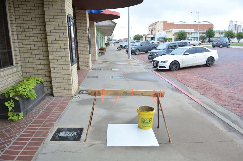 Poster board held down by a bucket and protected by a makeshift barricade cover the decorative tile recognizing professional boxer Lavern Roach on Plainview's Walk of Fame. It will be unveiled during a special dedication ceremony at 10:30 a.m. Saturday, Oct. 7, outside the Fair Theatre, 717 Broadway. The public is invited.