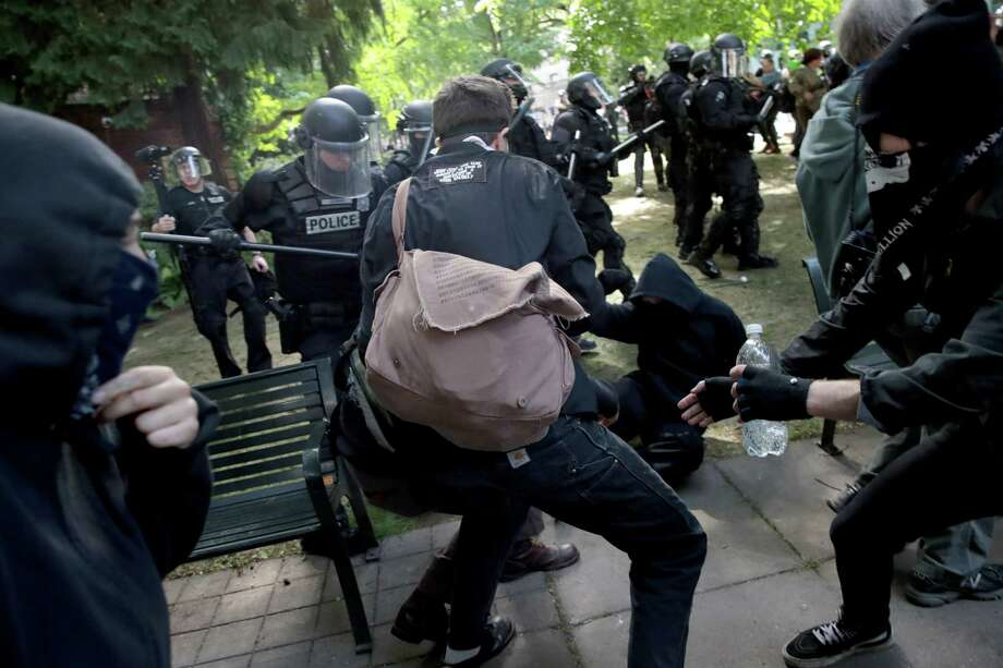 "Police clash with demonstrators as they try to clear 'Antifa' members and anti-Trump protesters from the area during a protest on June 4 in Portland, Oregon. Police used tear gas, flash bangs, and rubber bullets to clear the crowd. A protest dubbed ""Trump Free Speech"" by organizers was met by a large contingent of counter-demonstrators who viewed the protest as a promotion of racism. (Scott Olson/Getty Images)  ORG XMIT: MER2017060419304116 Photo: Scott Olson / 2017 Getty Images"