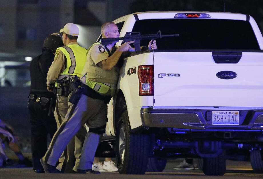 A police officer takes cover behind a truck at the scene of a shooting near the Mandalay Bay resort and casino on the Las Vegas Strip, Sunday, Oct. 1, 2017, in Las Vegas. Multiple victims were being transported to hospitals after a shooting late Sunday at a music festival on the Las Vegas Strip. (AP Photo/John Locher) Photo: John Locher, STF / Associated Press / Copyright 2017 The Associated Press. All rights reserved.