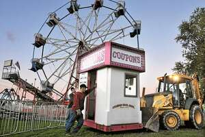Don Michaels, an employee of Coleman Bros. Shows, and Erick Johnson, a Portland Fair volunteer, guide Mike Lastrina, the director of grounds maintenance at the fair as he transports one of three ticketbooths in the carnival midway using a payloader in this October 2010 file photo.