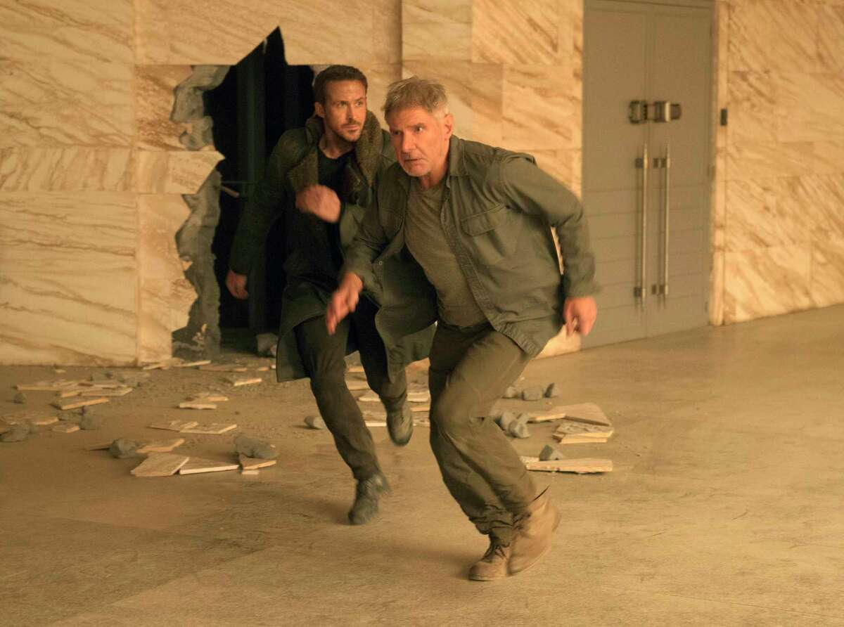 """This image released by Warner Bros. Pictures shows Ryan Gosling, left, and Harrison Ford in a scene from """"Blade Runner 2049."""" (Stephen Vaughan/Warner Bros. Pictures via AP) ORG XMIT: NYET730"""