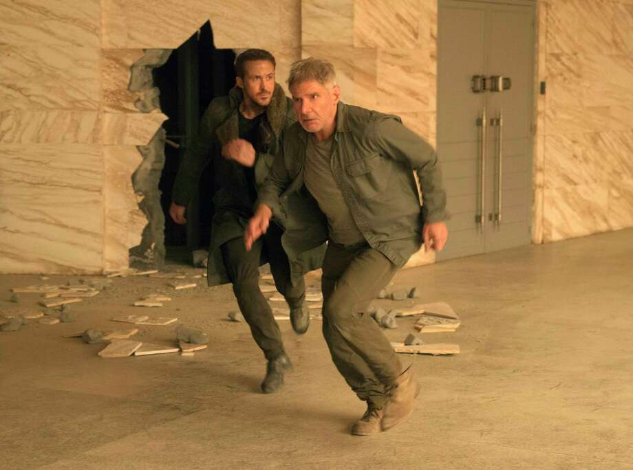 """This image released by Warner Bros. Pictures shows Ryan Gosling, left, and Harrison Ford in a scene from """"Blade Runner 2049."""" (Stephen Vaughan/Warner Bros. Pictures via AP) ORG XMIT: NYET730 Photo: Stephen Vaughan / © 2017 Warner Bros. Entertainment Inc. All Rights Reserved."""