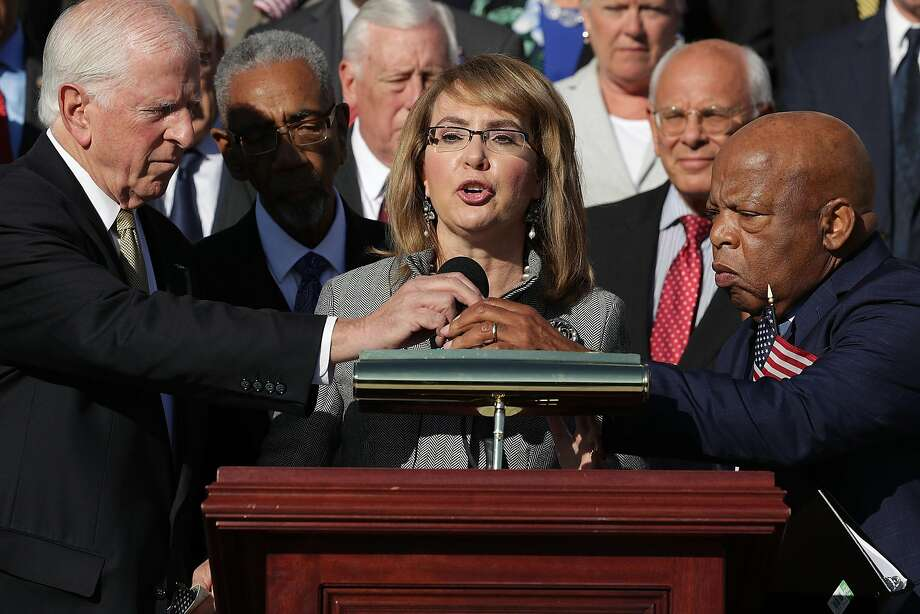 Rep. Mike Thompson, D-St. Helena, and Rep. John Lewis, D-Ga., adjust the microphone for former Congresswoman and gun violence victim Gabby Giffords as she addresses a rally with fellow Democrats on the East Front steps of the U.S. House of Representatives Oct. 4 in Washington, D.C. The Democratic members of Congress held the rally to honor to demand passage of the bipartisan King-Thompson legislation to strengthen background checks and establishing a bipartisan Select Committee on Gun Violence. Photo: Chip Somodevilla, Getty Images