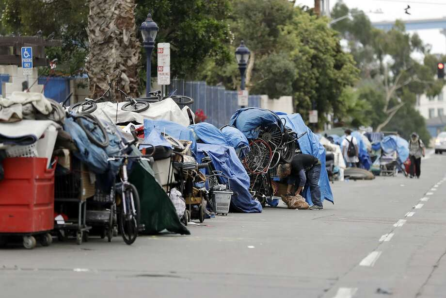 FILE-- In this Sept. 19, 2017 photo, homeless people stand among their items along 17th Street in San Diego. Police officers arrested at least a dozen people for feeding the homeless at an El Cajon city park. Photo: Gregory Bull, Associated Press