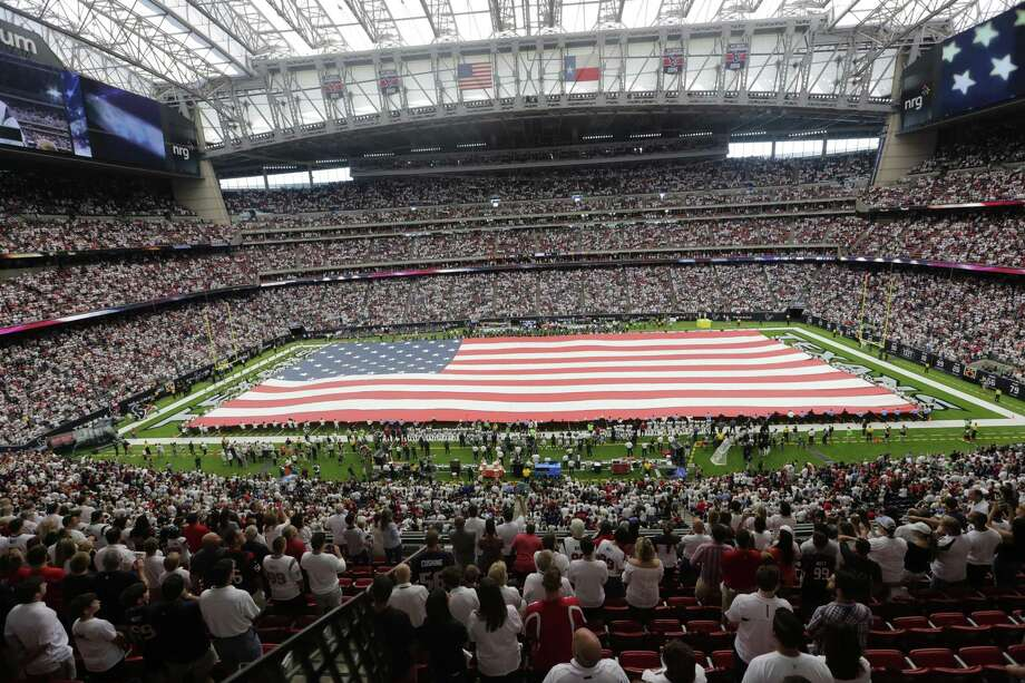 An An American flag drapes the field before an NFL football game between the Houston Texans and the Jacksonville Jaguars last month. Controversies over racial injustice — and how to deal with it — have ignited discussions about the flag and its place in American culture. Photo: Eric Gay /Associated Press / Copyright 2017 The Associated Press. All rights reserved.