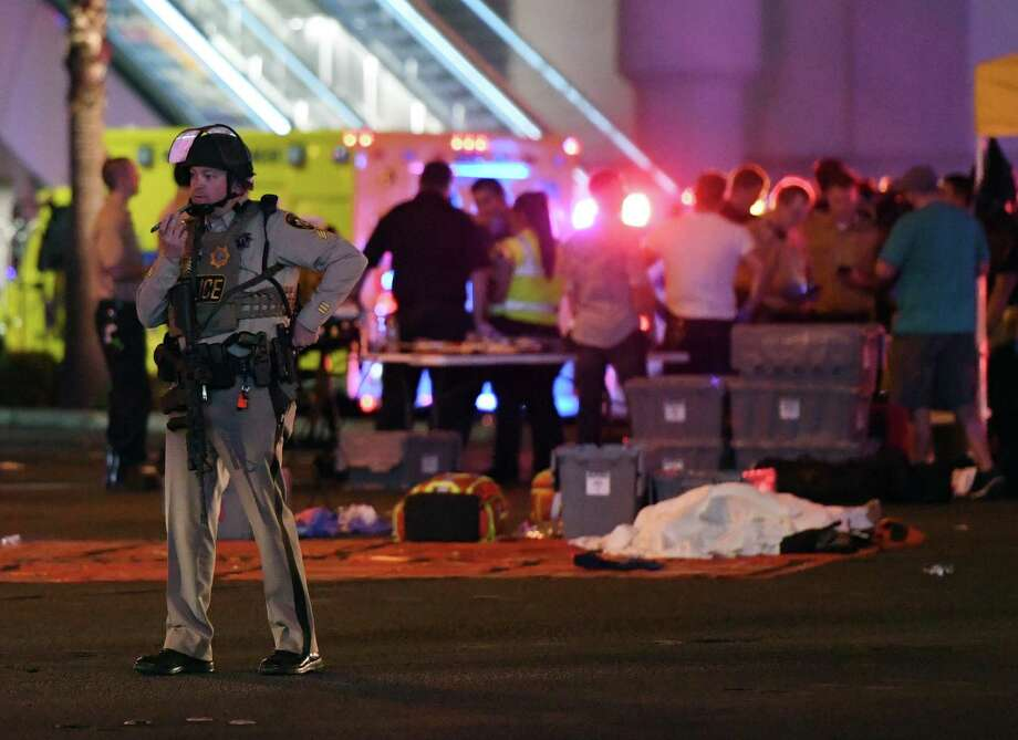 "A police officer stands on Las Vegas Boulevard after the mass shooting at a country music festival. The ""how"" of this tragedy is simple: Our nation is flooded with guns. Photo: Ethan Miller /Getty Images / 2017 Getty Images"