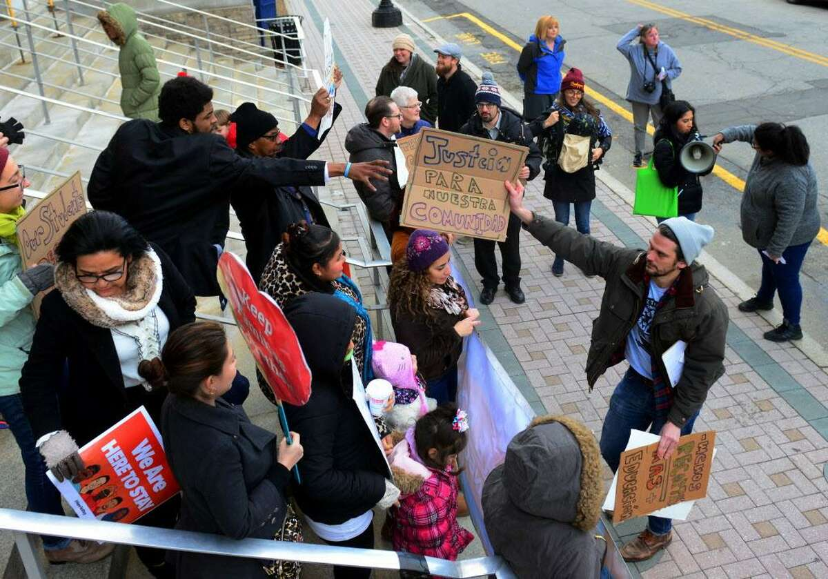 Julio Lopez Varona, Director of Make the Road Connecticut, at right, hands a sign to a participant for a rally held to support the Sanctuary designation for the city of Bridgeport in January.