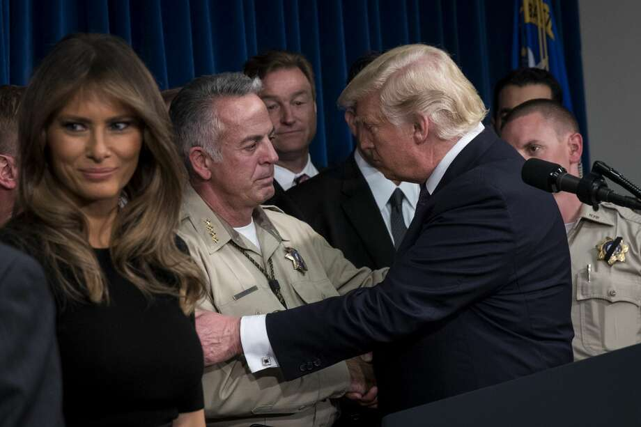(L-R) First lady Melania Trump looks on as Clark County Sheriff Joe Lombardo is embraced by President Donald Trump after the president delivered remarks in a room full of police officers and family members  at Las Vegas Metropolitan Police Department headquarters, October 4, 2017 in Las Vegas, Nevada. Trump is scheduled to visit with victims  and first responders from Sunday night's mass shooting during his trip to Las Vegas. Photo: Drew Angerer/Getty Images