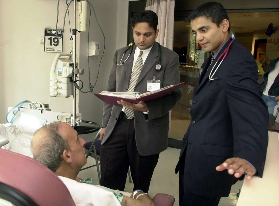 Dr. Samir P. Patel, right, is a hospitalist, a doctor who provides in-patient care in place of primary care physicians. Photo: MIKE DERER, AP