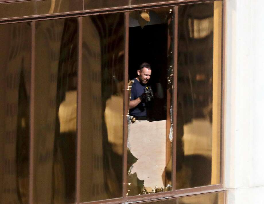 An investigator inspects the Las Vegas high-rise hotel room where a gunman opened fire, killing at least 59. Photo: Gregory Bull, Associated Press