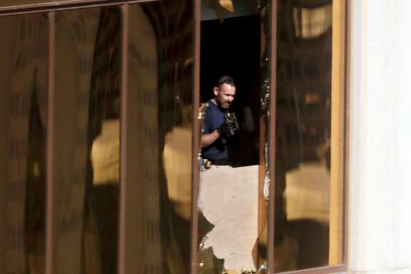 An investigator works in the room at the Mandalay Bay Resort and Casino where a gunman opened fire from on a music festival Wednesday, Oct. 4, 2017, in Las Vegas. The gunman killed dozens and injuring hundreds at the festival. (AP Photo/Gregory Bull)