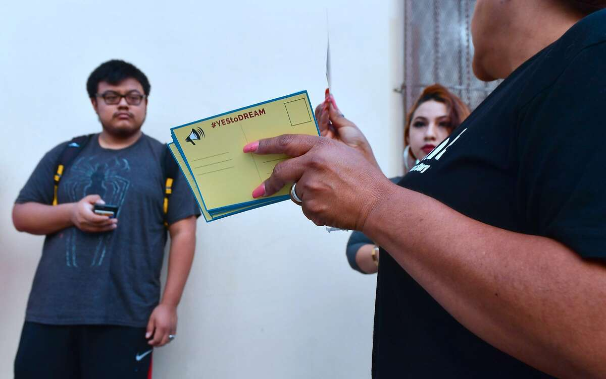 Volunteers offer cards to be filled out and sent to members of the House of Representatives as Deferred Action for Childhood Arrivals (DACA) recipients wait in line at the Coalition for Humane Immigrant Rights (CHIRLA) office in Los Angeles on September 30, 2017. Volunteer lawyers were on hand to offer assistance on the final weekend before the October 5, 2017, deadline when more than 154,000 DACA recipients must renew their work permits before the program ends March 5, 2018. / AFP PHOTO / FREDERIC J. BROWNFREDERIC J. BROWN/AFP/Getty Images