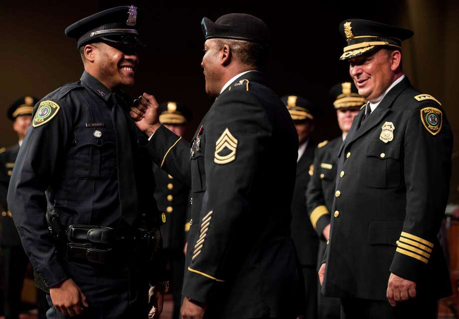 New Houston Police Officer Roham Walker, left, has his badge pinned on him by his father, Sgt. 1st Class Rohan Walker, as Chief Art Acevedo beams during Monday's graduation ceremony for the 59 officers frm HPD Cadet Class 232 at  Greater Grace Outreach Church. ( Brett Coomer / Houston Chronicle ) Photo: Brett Coomer, Staff / © 2017 Houston Chronicle