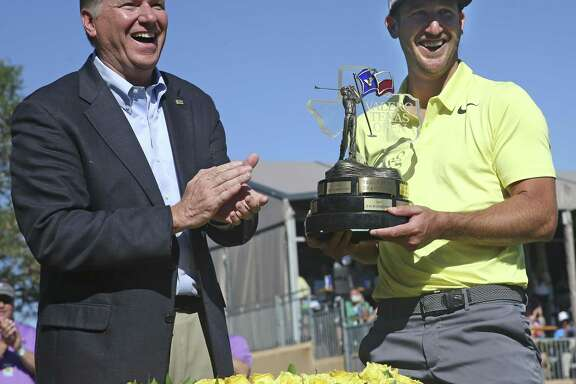 Kevin Chappell is handed the championship trophy by Gary Simmons of Valero after the final round of the Valero Texas Open at TPC San Antonio Oaks Course on April 23, 2017.