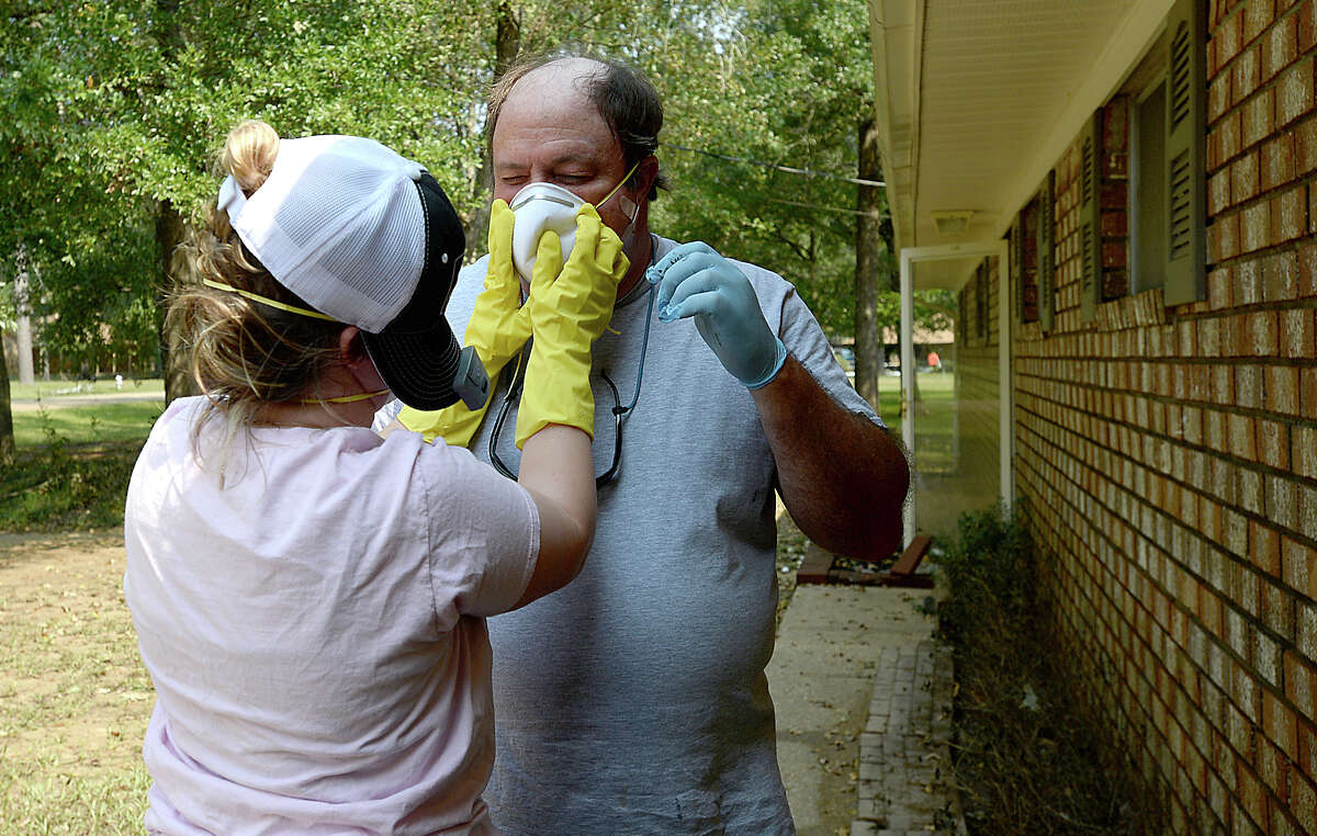 Carleigh Sutherland helps put a mask on her father Ernest LeDoux as the family get ready to clean their flood damaged Bevil Oaks home Wednesday. The community was cleared for entry Wednesday morning as flood waters have receded to safer levels throughout the majority of the community. Photo taken Wednesday, September 6, 2017 Kim Brent/The Enterprise