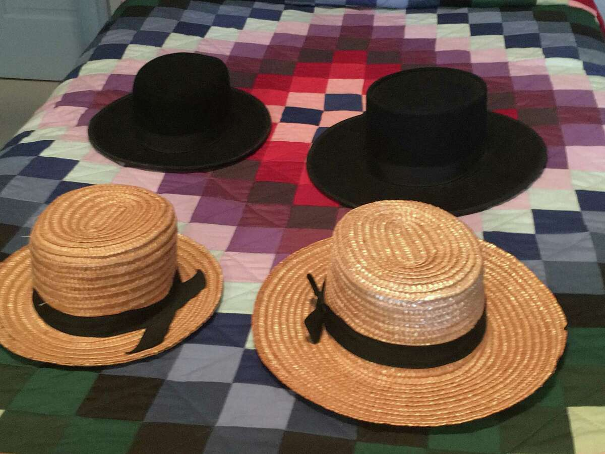 Amish men's everyday straw hats and dress hats sit on a typical Amish quilt.