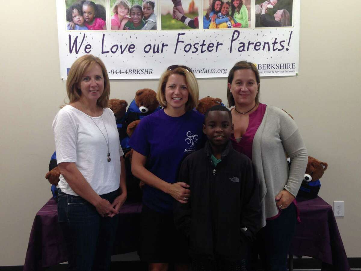 Suzanne Clarkson, Lower School director at Susan Odell Taylor School (second from left), poses with former student Jay Ross-Szczypinski and representatives from Berkshire Farm Center & Services for Youth. Students at the Troy school donated sweet cases for children entering the foster care system. (Submitted photo)