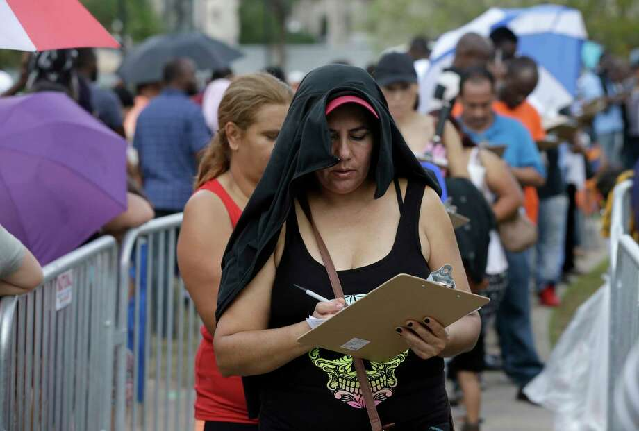 People fill out an application for the stateÕs Disaster Supplemental Nutrition Assistance Program as they wait in line outside the Southwest Multi-Service Center, 6400 High Star, Wednesday, Oct. 4, 2017, in Houston. People were given the forms near the front entrance. Thousands of people waited in a long line around the block to apply for D-SNAP, a short-term food assistance benefits to families recovering from a disaster. D-SNAP is only eligible to those who were not receiving SNAP food benefits at the time of the disaster. Photo: Melissa Phillip, Houston Chronicle / © 2017 Houston Chronicle