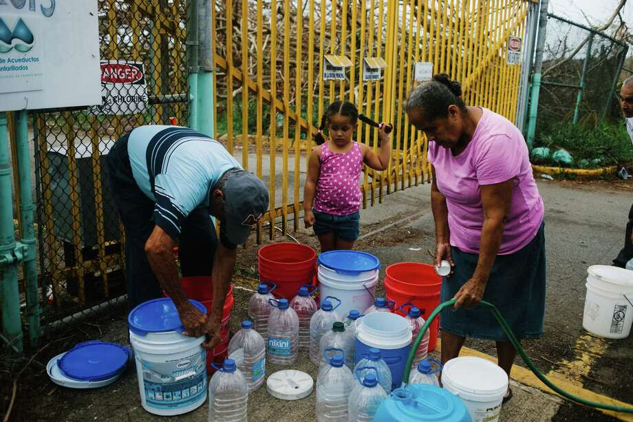 Residents fill containers with water at a center in Rio Grande, Puerto Rico, on Tuesday, Oct. 3, 2017. U.S. President Donald Trump visited storm-ravaged Puerto Rico on Tuesday, shook hands with the San Juan mayor he criticized on Twitter and remarked that relief costs could strain the federal budget. Photographer: John Taggart/Bloomberg ORG XMIT: 775053748 Photo: John Taggart / © 2017 Bloomberg Finance LP