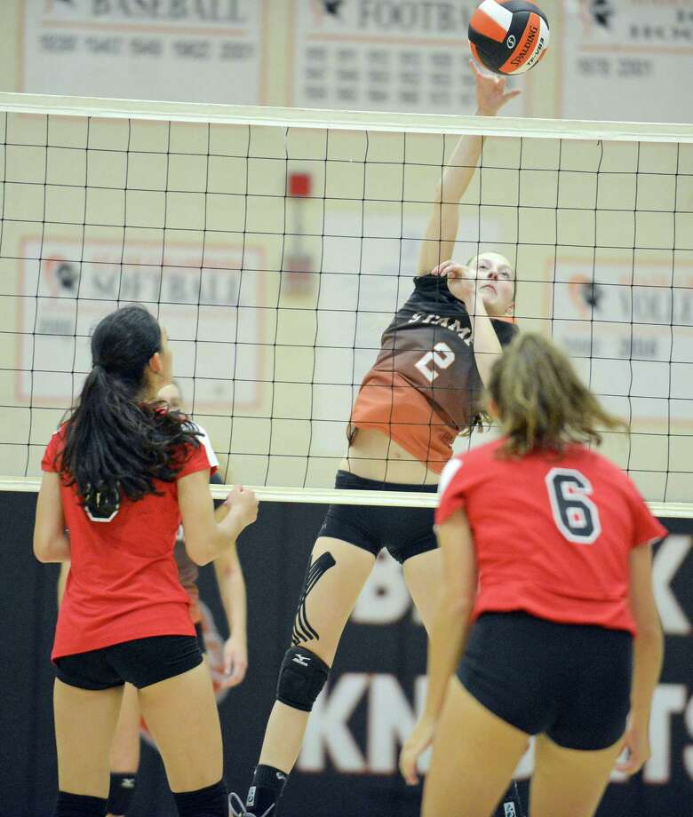 Stamford Megan Landsiedel taps the ball into play against Greenwich Erika Hauschild and Carolina Lew in an FCIAC girls volleyball match in Stamford, Connecticut on Wednesday, Oct. 4, 2017. Greenwich defeated Stamford 3-2. Photo: Matthew Brown / Hearst Connecticut Media / Stamford Advocate