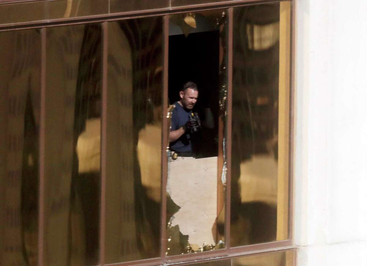 An investigator works in the room at the Mandalay Bay Resort and Casino where a gunman opened fire from on a music festival Wednesday, Oct. 4, 2017, in Las Vegas. The gunman killed dozens and injuring hundreds at the festival. (AP Photo/Gregory Bull) ORG XMIT: NVSM111