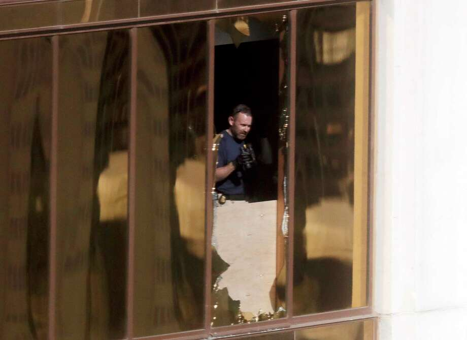 An investigator works in the room at the Mandalay Bay Resort and Casino where a gunman opened fire from on a music festival Wednesday, Oct. 4, 2017, in Las Vegas. The gunman killed dozens and injuring hundreds at the festival. (AP Photo/Gregory Bull) ORG XMIT: NVSM111 Photo: Gregory Bull / Copyright 2017 The Associated Press. All rights reserved.