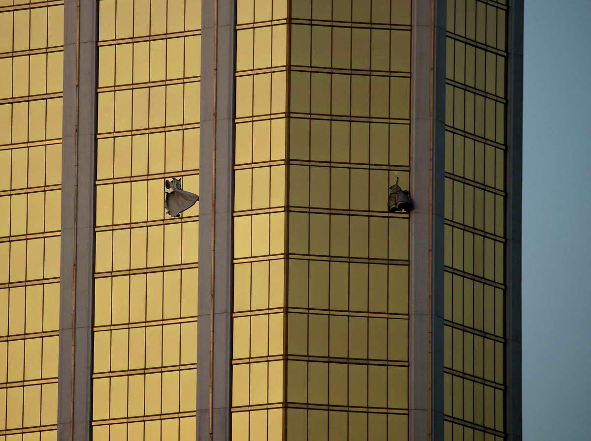 FILE - In this Monday, Oct. 2, 2017 file photo, drapes billow out of broken windows at the Mandalay Bay resort and casino on the Las Vegas Strip, following a mass shooting at a music festival in Las Vegas. From two broken-out windows of the resort, Stephen Craig Paddock had an unobstructed view to rain automatic gunfire on the crowd, with few places for them to hide. Sunday night?'s bloodbath left dozens of people dead and hundreds wounded. (AP Photo/John Locher, File) ORG XMIT: NYR301