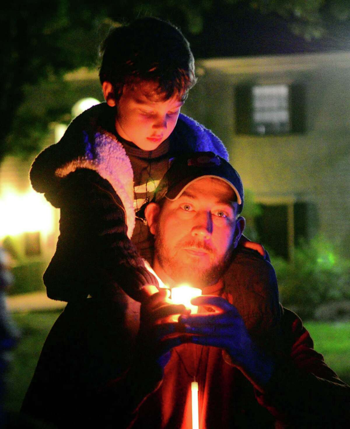 Matt Donovan, of Fairfield, and his son Liam, 5, attend a vigil to honor the victims and survivors of the mass shooting in Las Vegas at Burr Homestead in Fairfield, Conn. on Wednesday Oct. 4, 2017. The vigil was organized by CT Against Gun Violence.