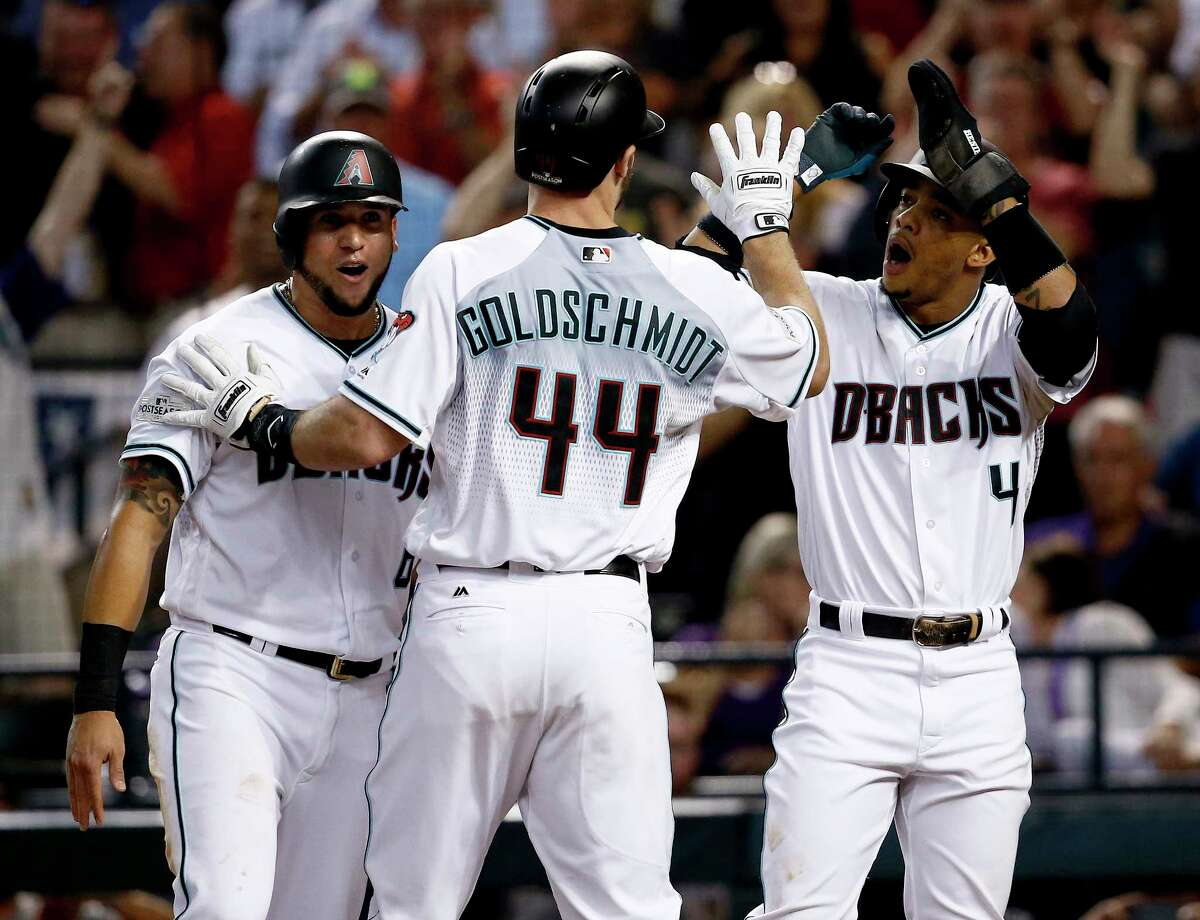 Arizona Diamondbacks' Paul Goldschmidt (44) high-fives Ketel Marte (4) and David Peralta after hitting a three run home against the Colorado Rockies during the first inning of the National League wild-card playoff baseball game, Wednesday, Oct. 4, 2017, in Phoenix. (AP Photo/Ross D. Franklin) ORG XMIT: AZMY113