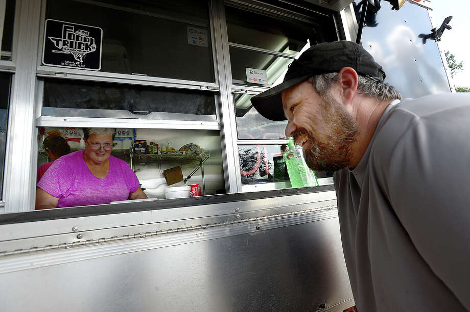 "Martha Vautrot greets regular customer Chris Andrews as he stops to pick up gumbo for dinner at Vautrot's food truck Wednesday. The family managed to borrow a cousin's food truck, which is only used during crawfish season, and re-opened for business in the lot behind the flood ravaged restaurant on US 105. Martha Vautrot and son Nicholas and employees had a huge turn out for Tuesday's opening, as word quickly spread on social media. ""People just kept coming, and by evening the place was full,"" Martha said. ""People were laughing, talking, sharing their own stories of loss. And they were seeing people they know,"" many of which they hadn't seen in a long time.  Nicholas added, ""everyone's sense of community is so fractured, that it's nice to have a place you know and where you can hang out."" ""My heart is full today,"" Martha said, after seeing so many of the community coming together again. ""I slept well for the first time last night."" Photo taken Wednesday, October 4, 2017 Kim Brent/The Enterprise Photo: Kim Brent / BEN"