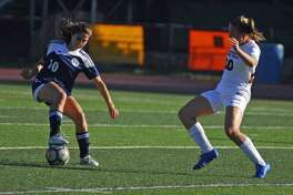Wilton's Zoe Lash, left, dribbles while Ridgefield's Megan Klosowski defends during a game on Wednesday.