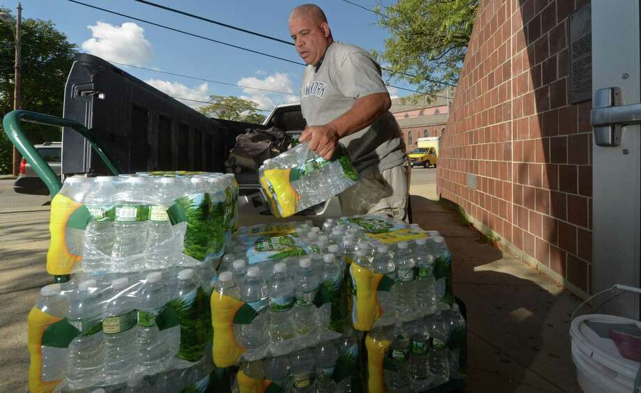 Norwalk Police Officer Hector Delgado unloads donations for storm ravaged Puerto Rico at the South Norwalk Community Center. It is just one of several local relief efforts. Photo: Erik Trautmann / Hearst Connecticut Media / Norwalk Hour