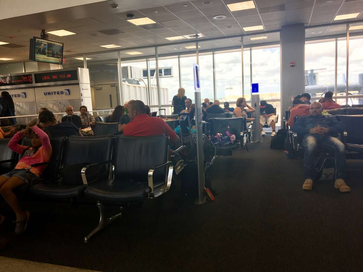 Passengers await news on the status of a flight from Houston to San Juan in Bush Intercontinental Airport on Thursday.