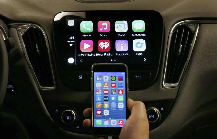 An iPhone is connected to a 2016 Chevrolet Malibu equipped with Apple CarPlay apps, displayed on the car's MyLink screen during a demonstration in Detroit. Automakers now include more infotainment options to allow drivers to use social media, email and text. The technology is also becoming more complicated to use. Photo: Paul Sancya /Associated Press / Copyright 2017 The Associated Press. All rights reserved.