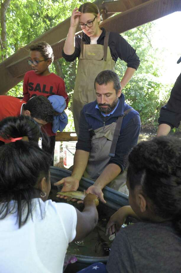 Brian Eltz and Mallory Humphrey, from the DEEP Fish Division, show Pembroke School students fish taken from the Still River during the Housatonic Valley Association (HVA) Still River Day. The event is used to teach Danbury middle and elementary school students about the environment in an outdoor classroom setting next to the Still River. Wednesday, October 4, 2017, in Danbury, Conn. Photo: H John Voorhees III / Hearst Connecticut Media / The News-Times