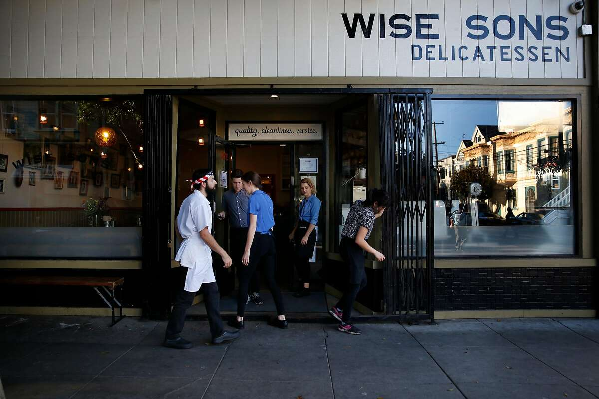 Joey Boujo (l to r), sous chef; Noah Brau, host; , Alex Limon, server; Amanda Rino, project manager and Nicole Gintu, server work together to figure out the locking mechanism on the front gate as they open for dinner, a recent Wise Sons Jewish Delicatessen addition after over 2 years in business, at Wise Sons Jewish Delicatessen on Thursday, October 2, 2014 in San Francisco, Calif.